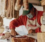butcher slicing salami in their Gastronomy with a covid mask